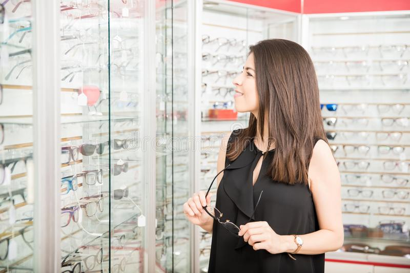 Side view of beautiful woman trying on glasses in optician store stock image