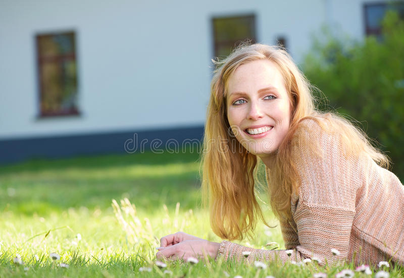 Happy young woman smiling and relaxing on grass outdoors royalty free stock image