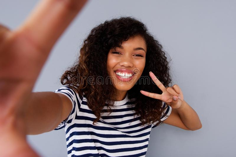 Happy young woman smiling and taking selfie. Portrait of happy young woman smiling and taking selfie royalty free stock images
