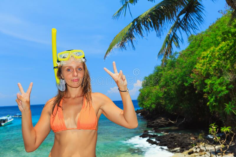 Happy young woman in snorkeling mask on tropical island beach. Happy family - active young woman in snorkeling mask. Sea lagoon beach scenic view, tropical royalty free stock photography