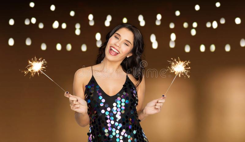 Happy young woman with sparklers at party royalty free stock photo