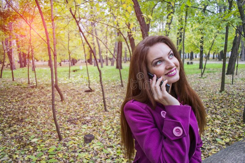 Happy young woman speaks on a smartphone in the autumn park. royalty free stock photo