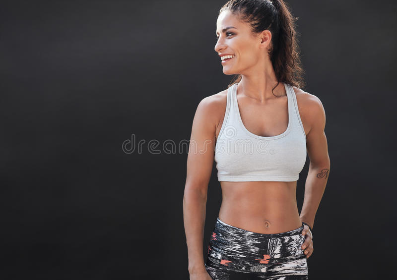 Happy young woman in sports clothing smiling. Muscular fitness model on black background looking away at copy space royalty free stock images