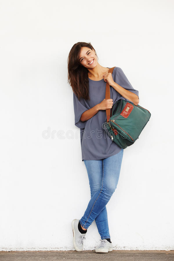 Happy young woman standing against wall and smiling. Full body portrait of happy young woman standing against wall and smiling stock photo