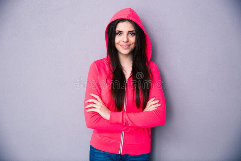 Happy young woman standing with arms folded. Over gray background. Looking at camera stock photography