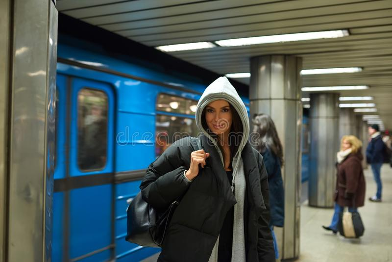 A happy young woman standing in front of a subway train royalty free stock images