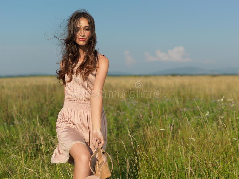 Happy, young woman standing in green field stock image