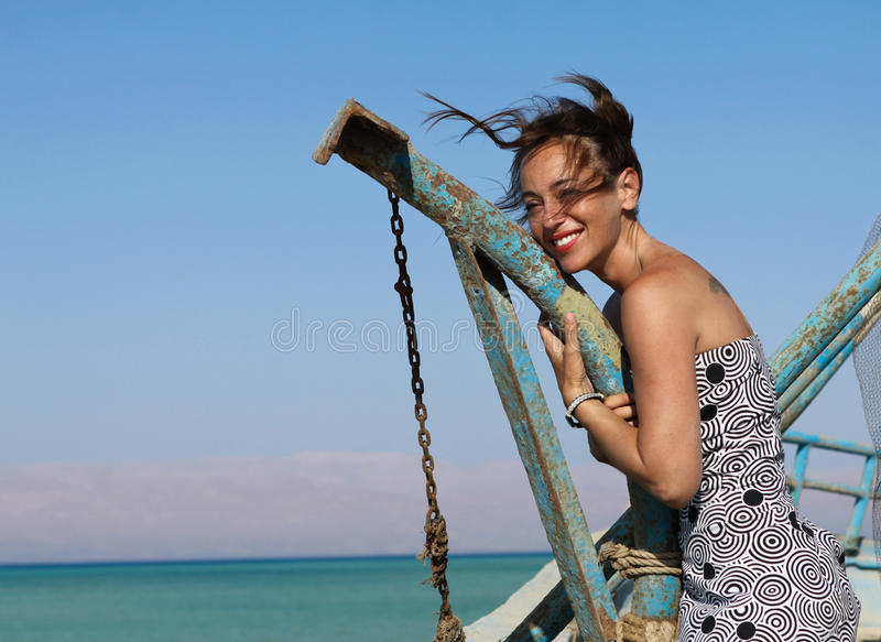 Happy young woman standing on an old boat stock image