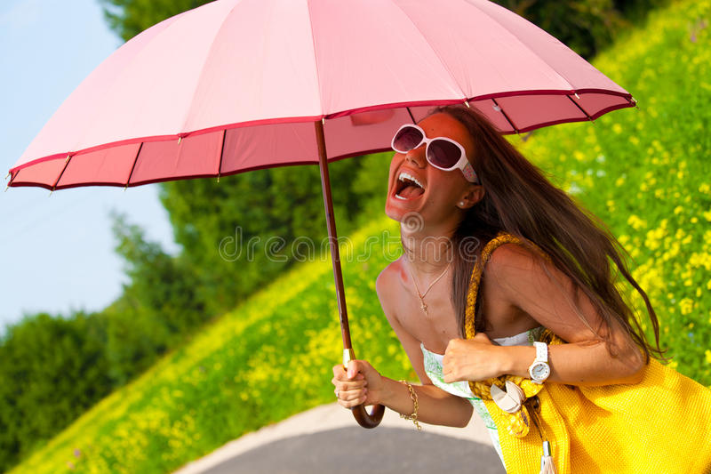 Happy young woman standing with a pink umbrella royalty free stock photos