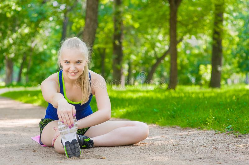 Happy young woman stretching before running outdoors royalty free stock photos