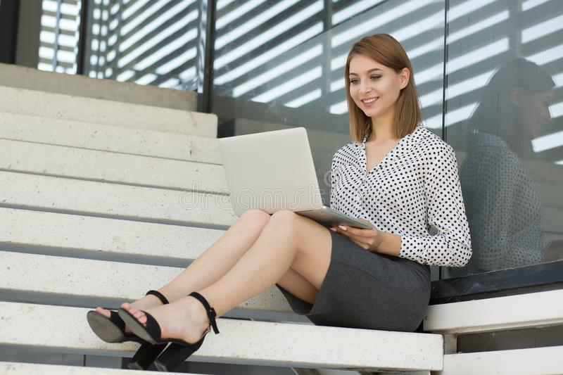 Happy young woman student with red curly hair working typing laptop, sitting on block stairs and looking with smile to desktop. royalty free stock photography