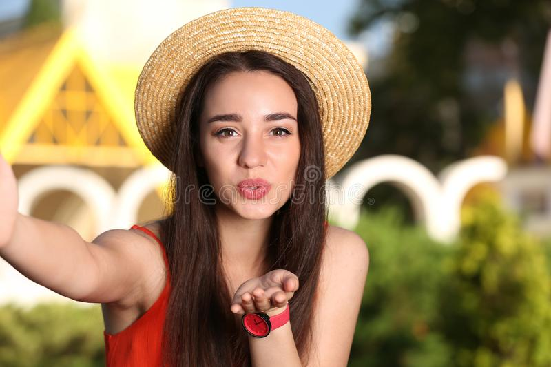 Happy young woman in stylish hat taking selfie on sunny day royalty free stock images