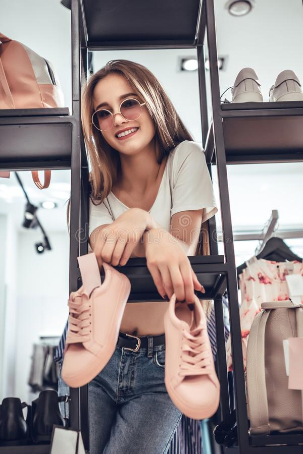 Happy young woman in sunglasses customer choosing pair of sneakers shoes and buying it in clothes store. Casual shopping concept. Storefront with shoes stock images