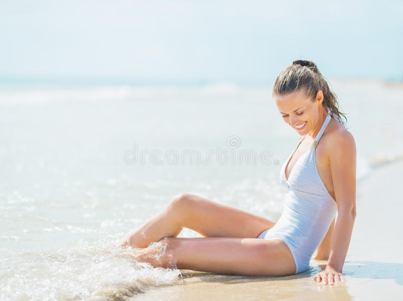 Happy young woman in swimsuit enjoying sitting in sea water stock photography