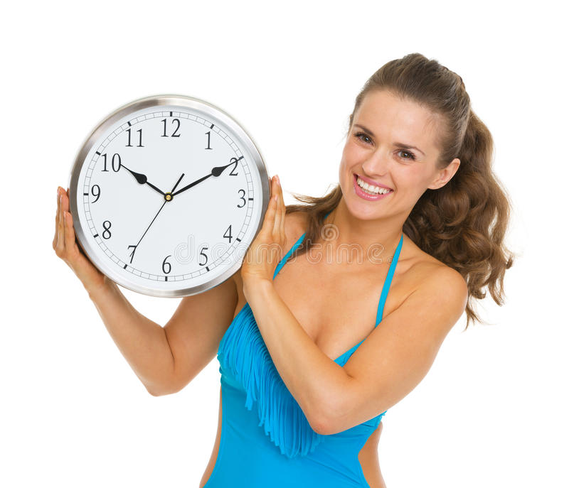 Happy young woman in swimsuit showing clock. Isolated on white royalty free stock photos