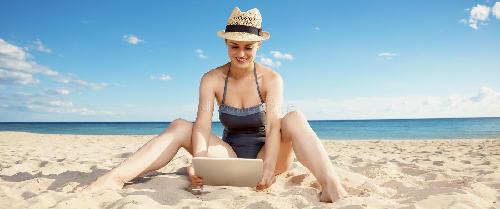Happy young woman in swimwear on beach using tablet PC royalty free stock image