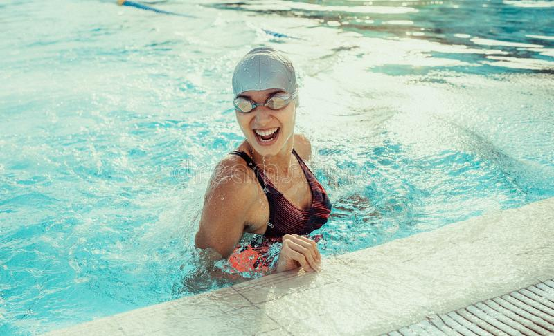 Professional swimmer smiling in pool. Happy young woman in swimwear laughing at the edge of the pool. Smiling professional swimmer in pool royalty free stock photo