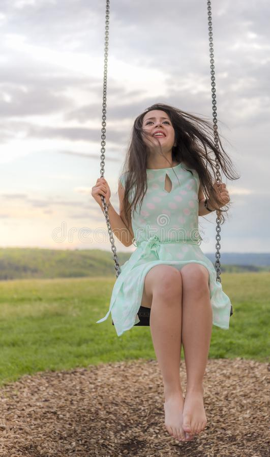 Happy young woman on a swing at sunset royalty free stock image