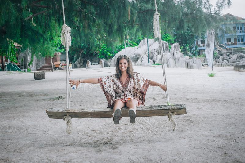 Happy young woman swinging on the swing at tropical beach. Koh Tao, Thailand royalty free stock photos