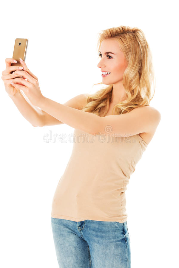 Happy young woman taking pictures of herself at smart phone stock images