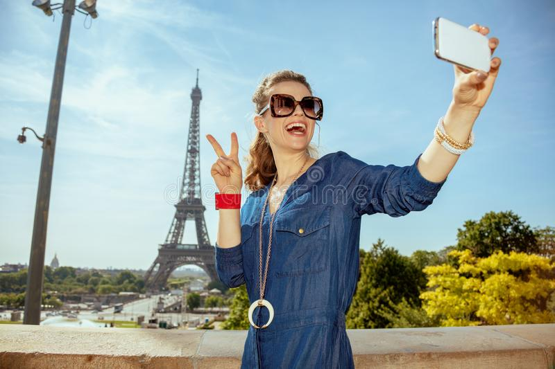 Happy young woman taking selfie with phone and showing victory. Happy young woman in blue jeans overall taking selfie with smartphone and showing victory gesture royalty free stock images