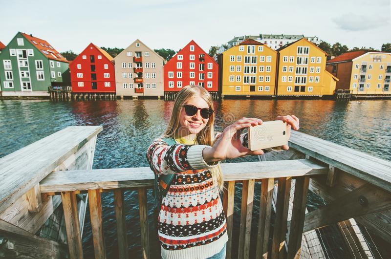 Happy young woman taking selfie positive smiling. Traveling in Trondheim city Norway vacations weekend Lifestyle fashion outdoor scandinavian houses landmarks royalty free stock photo