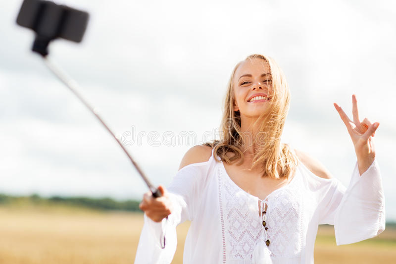 Happy young woman taking selfie by smartphone. Technology, summer holidays, vacation and people concept - smiling young woman in white dress taking picture by royalty free stock photography