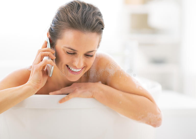 Happy Young Woman Talking Cell Phone In Bathtub Stock Photo