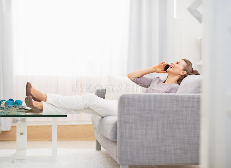 Happy young woman talking cell phone while sitting on sofa royalty free stock photos