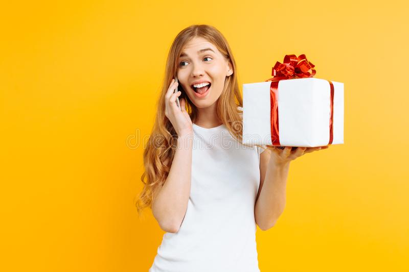 Happy young woman talking on a mobile phone, shows a gift box, on a yellow background royalty free stock photo