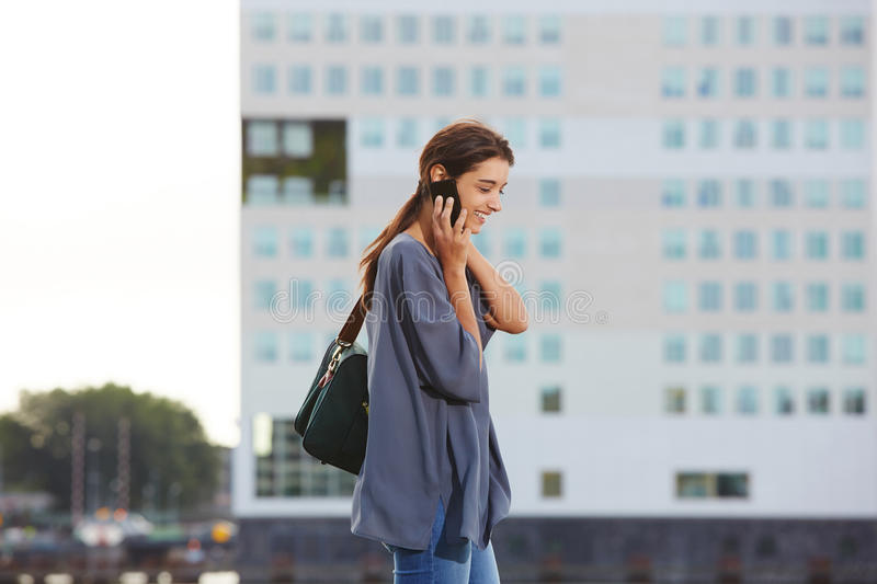 Happy young woman talking on smartphone outdoors in city. Side portrait of happy young woman talking on smartphone outdoors in city royalty free stock photography