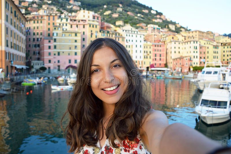 Happy young woman tanned taking selfie photo in a typical italian landscape with harbour and colorful houses for italian holidays royalty free stock image