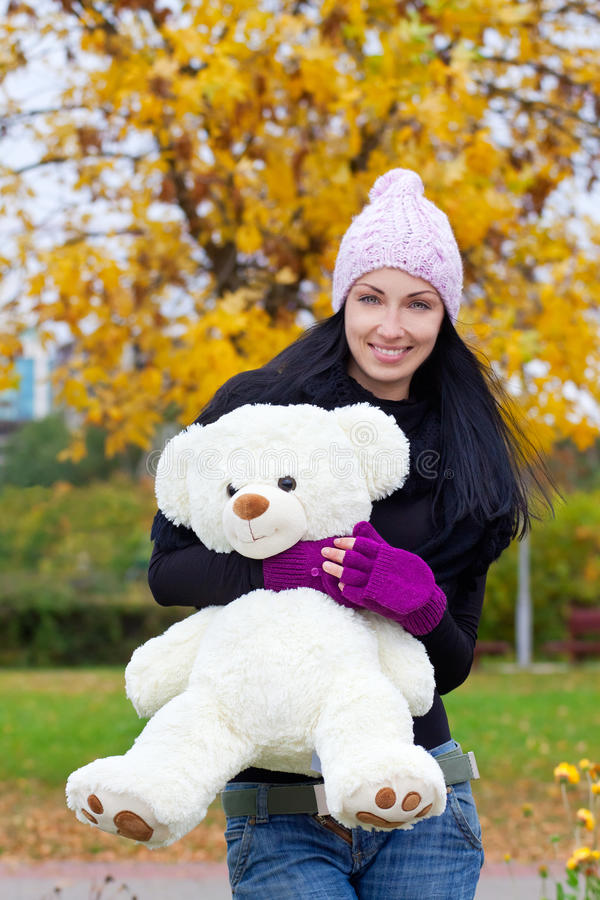 Happy young woman with a teddy bear stock image