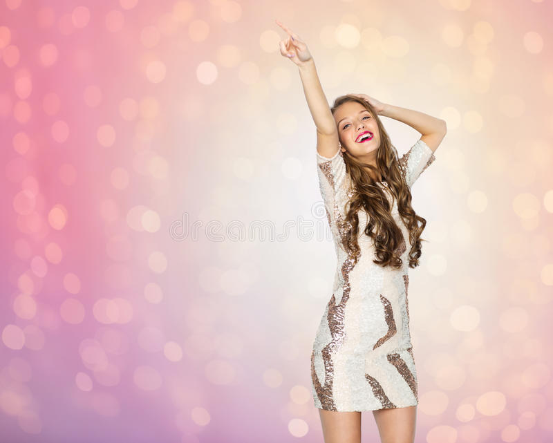 Happy young woman or teen girl dancing at party. People, style, holidays and fashion concept - happy young woman or teen girl in fancy dress with sequins and royalty free stock photo