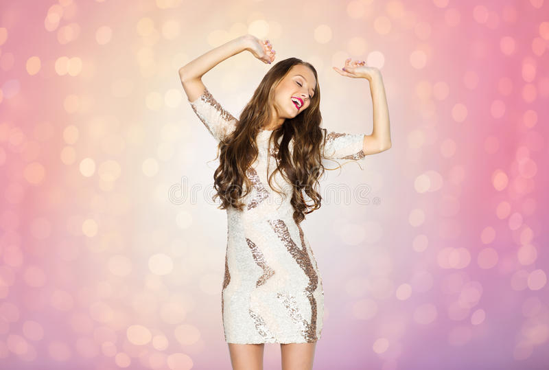 Happy young woman or teen girl dancing at party. People, style, holidays and fashion concept - happy young woman or teen girl in fancy dress with sequins and royalty free stock image
