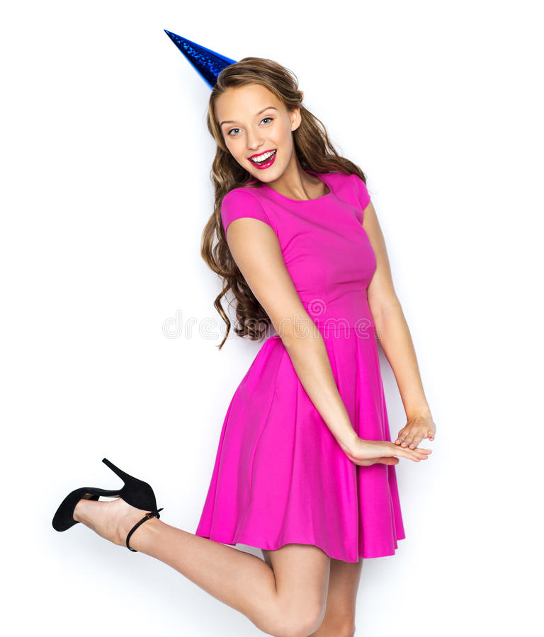 Happy young woman or teen girl in party cap. People, holidays and celebration concept - happy young woman or teen girl in pink dress and party cap stock image