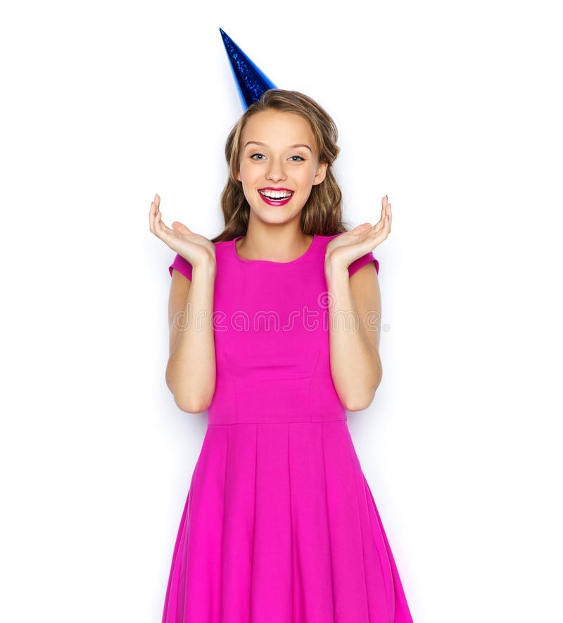 Happy young woman or teen girl in party cap. People, holidays and celebration concept - happy young woman or teen girl in pink dress and party cap stock photography