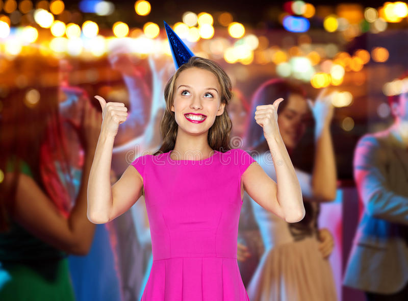 Happy young woman or teen girl in party hat. People, holidays and celebration concept - happy young women or teen girl in pink dress and party hat showing thumbs stock photo