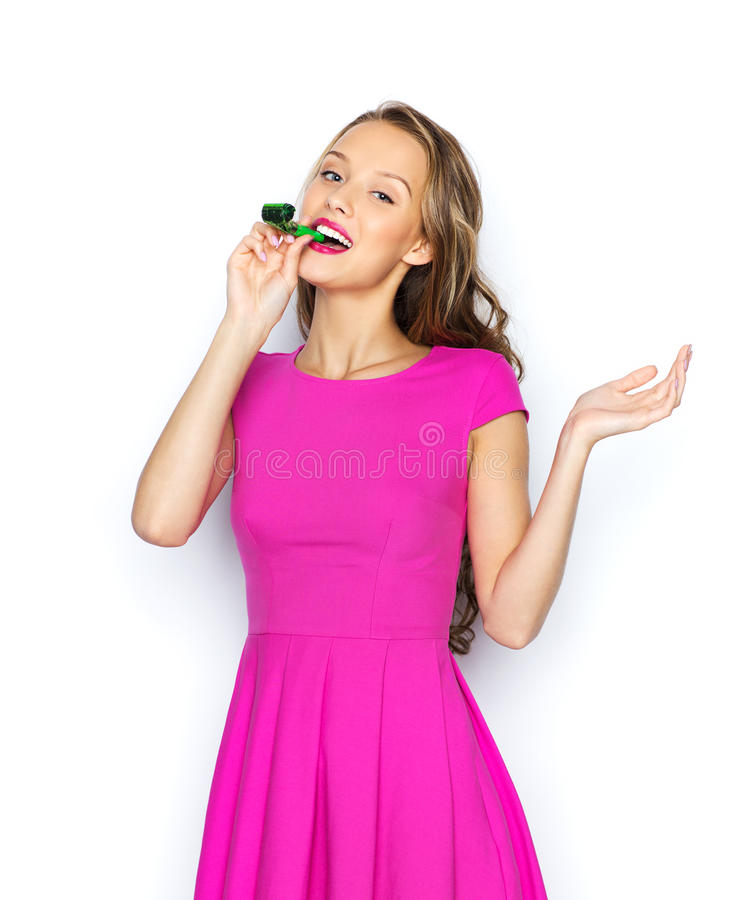 Happy young woman or teen girl with party horn. People, holidays and celebration concept - happy young woman or teen girl in pink dress and party cap stock photography