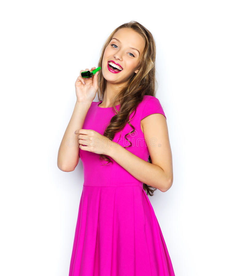Happy young woman or teen girl with party horn. People, holidays and celebration concept - happy young woman or teen girl in pink dress and party cap stock images