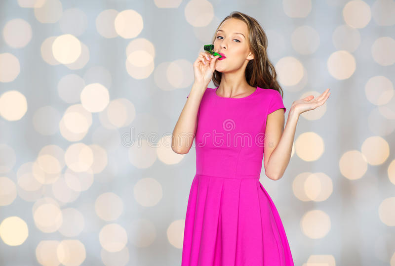 Happy young woman or teen girl with party horn. People, holidays and celebration concept - happy young woman or teen girl in pink dress and party cap over lights royalty free stock photography