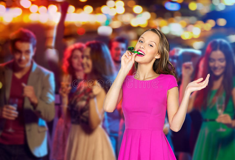 Happy young woman or teen girl with party horn. People, holidays and celebration concept - happy young women or teen girl in pink dress blowing to party horn at stock photos