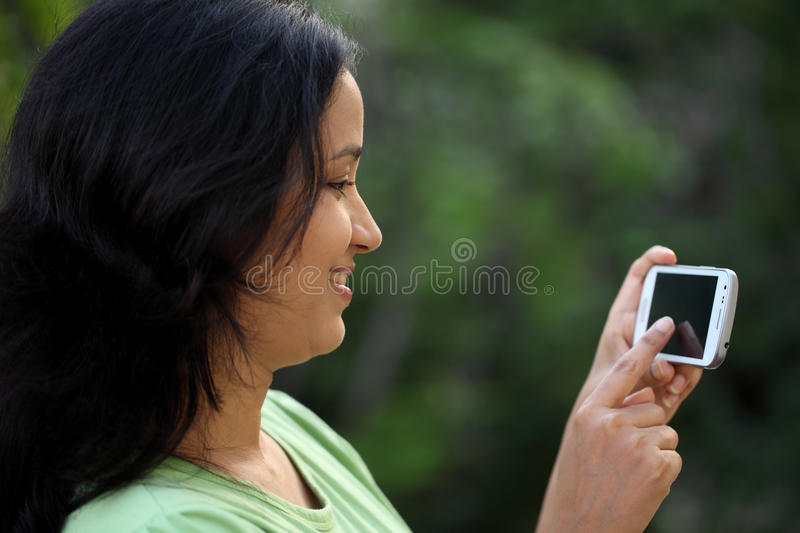 Happy young woman text messaging royalty free stock photography