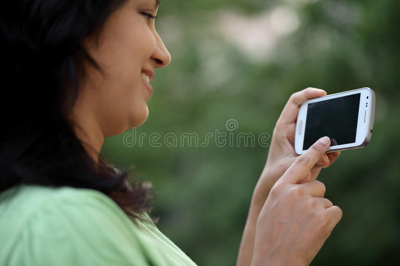 Happy young woman text messaging stock image
