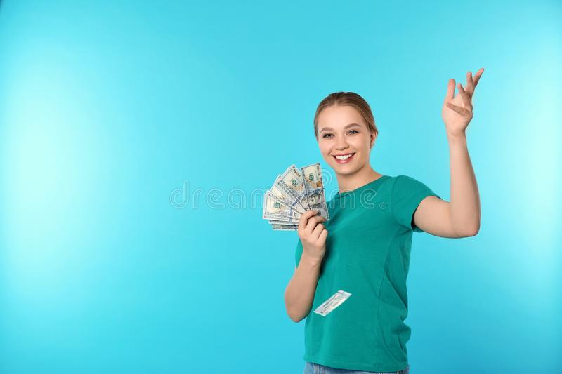 Happy young woman throwing money on color background stock image