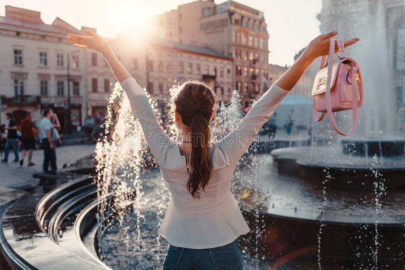 Happy young woman tourist looks at fountain. Summer travel. Vacation and holidays concept royalty free stock images