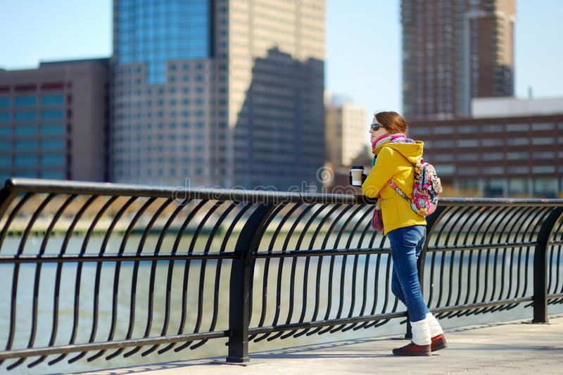 Happy young woman tourist sightseeing in New York City at sunny spring day. Female traveler drinking coffee in downtown Manhattan. Travelling in USA stock image
