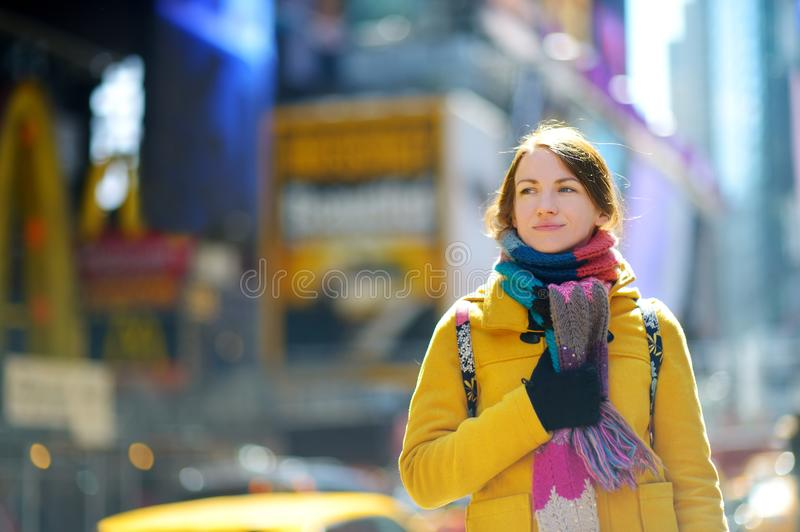 Happy young woman tourist sightseeing at Times Square in New York City. Female traveler enjoying view of downtown Manhattan. Travelling in USA royalty free stock photography
