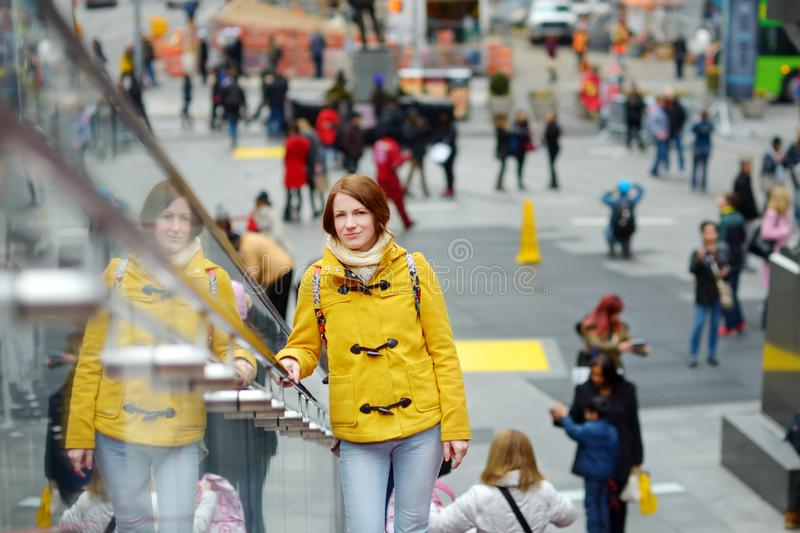 Happy young woman tourist sightseeing at Times Square in New York City. Female traveler enjoying view of downtown Manhattan. Travelling in USA royalty free stock photos