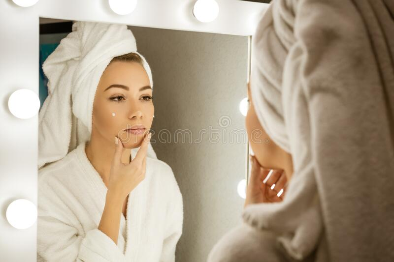 A happy young woman in a towel in front of a mirror applies cream to her face, a concept of skin care at home.  stock photo